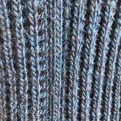 Detalje af blå hulmønster sweater
